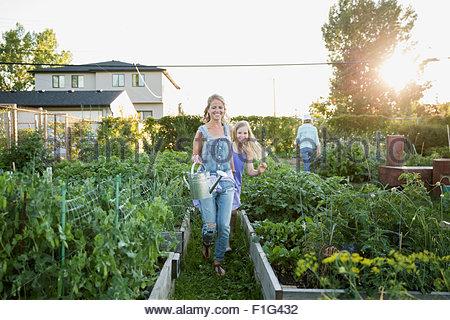 Mère et fille marcher avec arrosoir jardin Banque D'Images