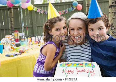 Portrait mère et enfants gâteau d'anniversaire avec jardin Banque D'Images