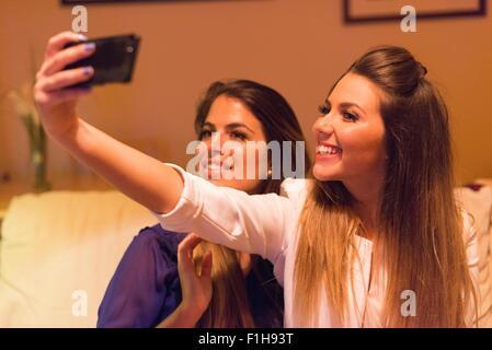 Deux jeunes femmes, taking self portrait à l'aide de smartphone Banque D'Images