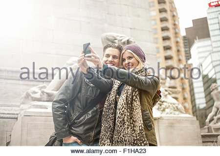 Couple selfies sur smartphone Street, New York, USA Banque D'Images