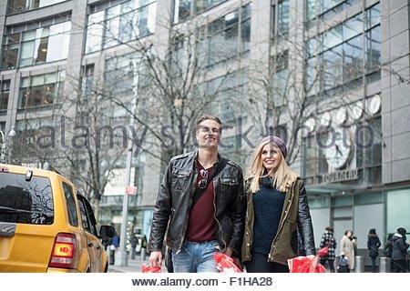 Jeune couple strolling shopping sur street, New York, USA Banque D'Images
