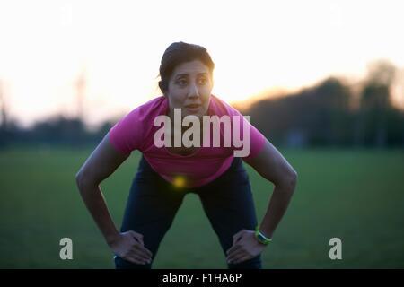 Femme mature de prendre une pause à partir de l'exercice dans park