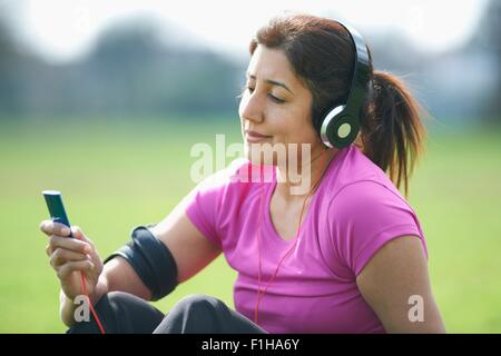 Femme mature en pause dans la sélection de la musique du lecteur MP3