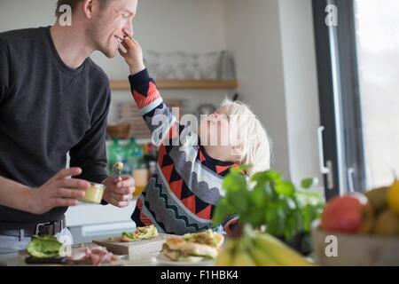 Boy touching visage du père dans la cuisine Banque D'Images