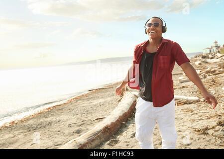 Young man standing on beach portant des écouteurs et des lunettes
