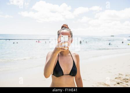 Young woman wearing bikini top prenant selfies smartphone sur la plage de Waikiki, Hawaii, USA Banque D'Images