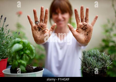 Mid adult woman holding sol couvert hands up Banque D'Images