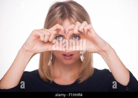 Femme blonde faire un cœur avec ses mains Banque D'Images