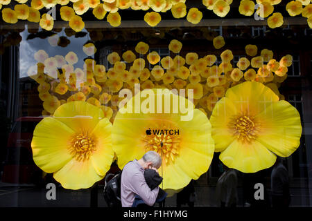Homme avec doigt dans son oreille en face de l'affichage de la fenêtre Regarder Apple dans Selfridges, le centre Banque D'Images