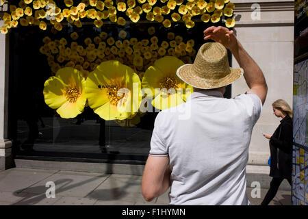 L'homme à chapeau de paille en face de l'affichage de la fenêtre Regarder Apple dans Selfridges, le centre de Londres. Banque D'Images