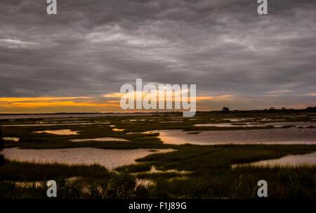 Des couchers de soleil comme les nuages menaçants d'incandescence rouler dans plus de Assateague Island Banque D'Images