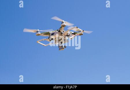 Quadrocopter Camouflage planant contre un ciel bleu avec d'atterrissage Banque D'Images