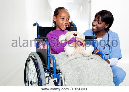 Un médecin en poussant un girl holding a teddy dans un fauteuil roulant Banque D'Images