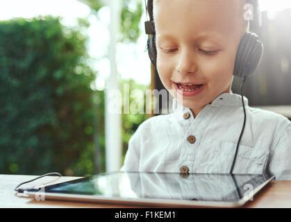 Adorable petit garçon à l'écoute de la musique enregistrée sur sa tablette ordinateur à l'aide d'un casque avec Banque D'Images