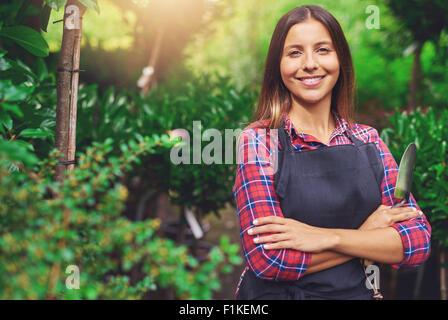 Smiling young woman enjoying son jardin debout les bras croisés contre un écrin de verdure avec une truelle à la Banque D'Images