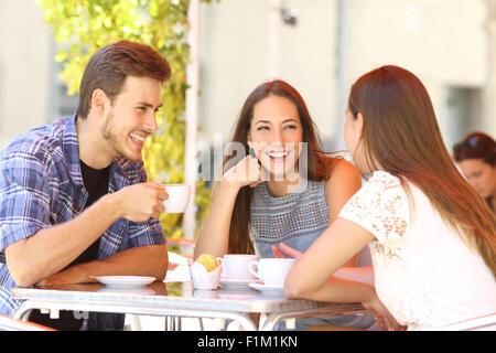Trois amis heureux parler et rire dans un café terrasse