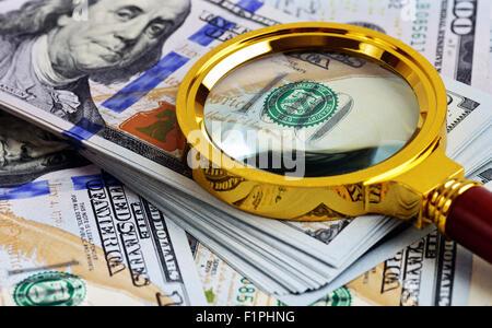 L'analyse des investissements. Pile de Dollar et loupe Banque D'Images