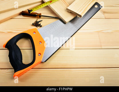 Vis, scie, ruban de mesure et d'un marteau sur le bois Banque D'Images