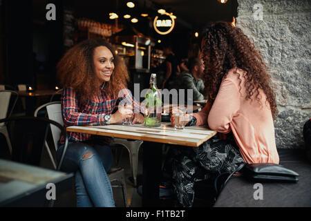 Deux jeunes femmes parlant assis dans un restaurant. African woman smiling et discutant avec son ami dans un café. Banque D'Images