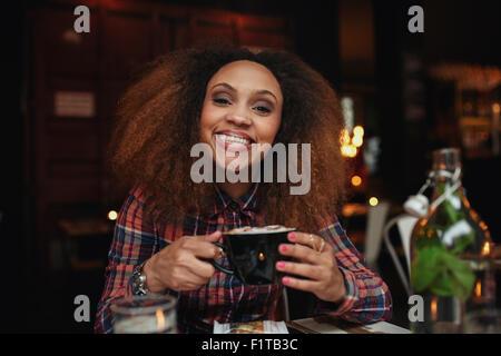Portrait de jeune femme de boire du café. African woman sitting at cafe tenant une tasse de café, souriant. Banque D'Images