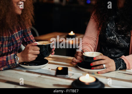 Cropped shot of two women sitting holding tasse de café. Les amis de boire du café à une table Banque D'Images