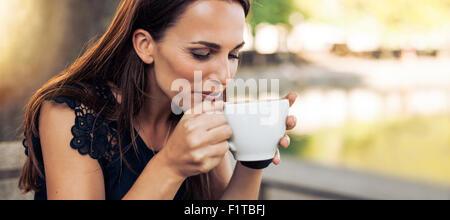 Portrait de jeune femme avec un café aromatique dans les mains. Femme de boire du café au café. Banque D'Images