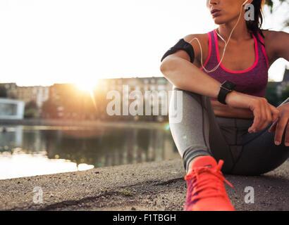 Jeune femme runner se reposant après séance d'entraînement sur matin ensoleillé. Modèle de remise en forme féminine Banque D'Images