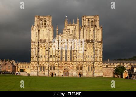 La lumière du soleil à l'Ouest l'avant de la cathédrale de Wells, Somerset UK contre un ciel gris orageux, Wells, Somerset, England UK