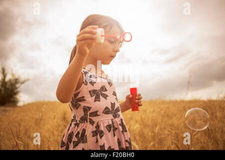 Girl blowing bubbles in wheat field Banque D'Images
