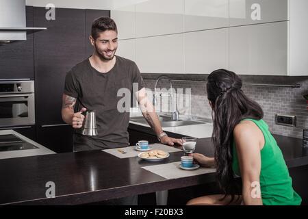 Jeune homme verser du café de petit-déjeuner pour l'amie Banque D'Images
