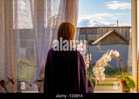 Woman looking out au bâtiment agricole à partir de la fenêtre du salon Banque D'Images