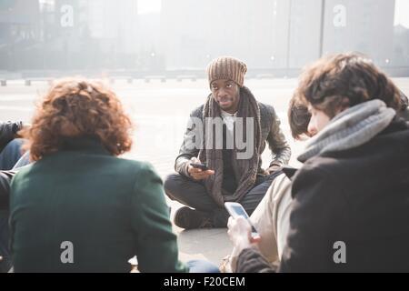 La mise en réseau d'amis des jeunes adultes assis sur les smartphones Banque D'Images