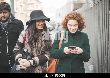 Deux jeunes femmes se promener le long de la lecture de textes de la rue smartphone Banque D'Images