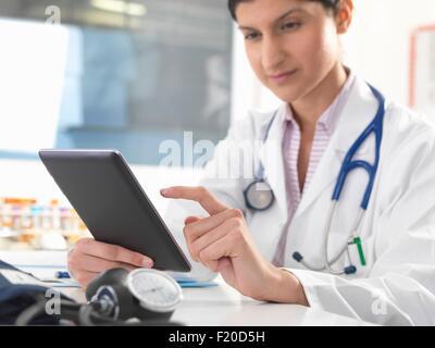 Femme médecin mise à jour des dossiers médicaux sur tablette numérique Banque D'Images