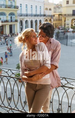 Couple hugging on restaurant balcon sur la Plaza Vieja, La Havane, Cuba Banque D'Images
