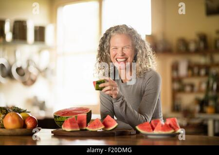 Portrait of young woman eating watermelon in kitchen Banque D'Images