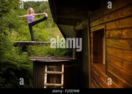 Young woman posent sur la passerelle à l'eco lodge Banque D'Images