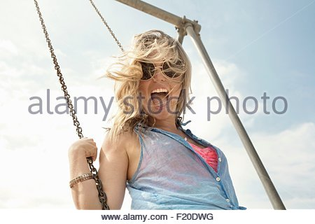 Portrait of young woman swinging on swing Banque D'Images