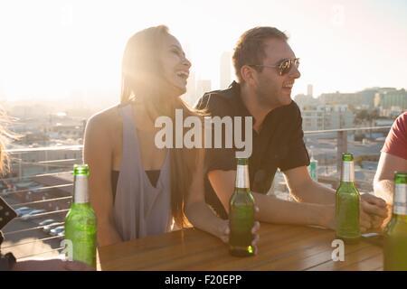 Deux amis adultes de boire une bière au bar en terrasse avec table Los Angeles skyline, USA Banque D'Images