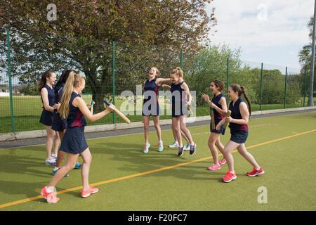 Groupe de filles sur terrain de sport avec des battes de base-ball
