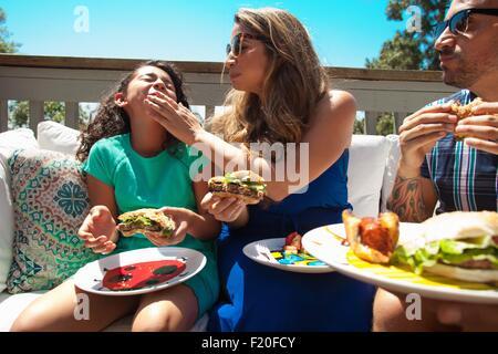 Mère Fille d'alimentation aliments barbecue in garden Banque D'Images