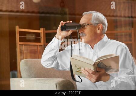 Senior man at home, l'observation des oiseaux par la fenêtre, à l'aide de jumelles Banque D'Images