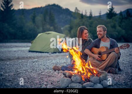 Jeune couple assis par camp à jouer de la guitare Banque D'Images