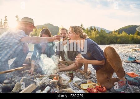 Alimentation man woman sur un feu de camp Banque D'Images