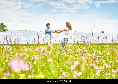 Young couple holding hands in field, à côté de la ferme solaire Banque D'Images