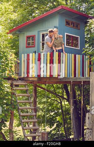 Jeune couple standing in tree house, étreintes, laughing Banque D'Images