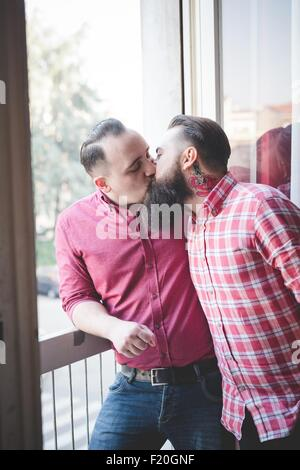 Gay couple kissing by window Banque D'Images
