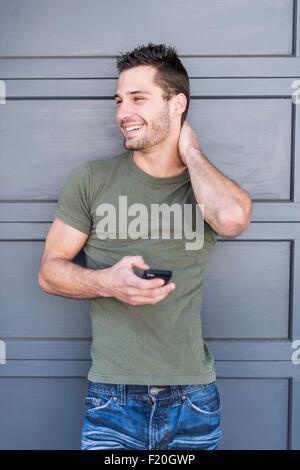 Portrait de jeune homme avec le smartphone appuyé contre porte grise Banque D'Images