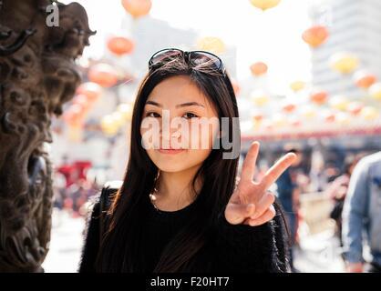 Portrait de jeune femme avec de longs cheveux et des lunettes sur la tête faisant signe de paix, looking at camera Banque D'Images