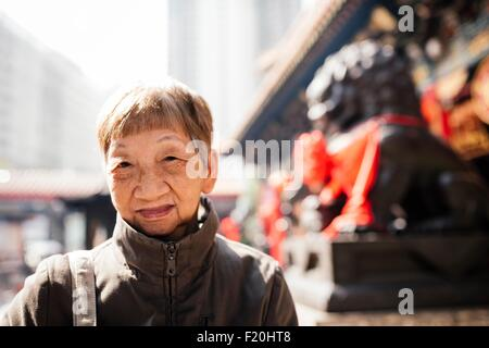 Portrait of senior woman wearing manteau en face de lion statue, looking at camera Banque D'Images